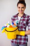 Giovani strumenti e prodotti graziosi di pulizia della tenuta della donna in secchio Fotografia Stock Libera da Diritti