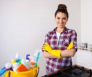 Giovani strumenti e prodotti graziosi di pulizia della tenuta della donna in secchio Fotografia Stock