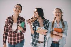 Giovani studentesse allegre con i manuali in mani Immagine Stock