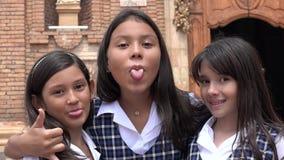 Giovani studentesse colombiane che fanno i fronti divertenti che portano gli uniformi scolastichi Immagine Stock