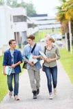 Giovani studenti che camminano fuori della città universitaria Immagini Stock