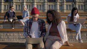 Giovani studenti che lavorano con computer portatili all'aperto stock footage