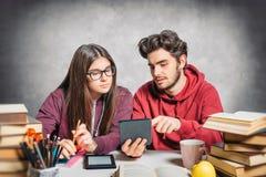 Giovani studenti che leggono un libro elettronico Fotografia Stock