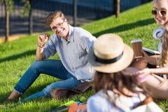 Giovani studenti che parlano mentre sedendosi sull'erba verde in parco Immagini Stock Libere da Diritti