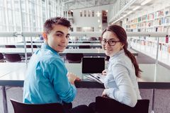 Giovani studenti che studiano con il pc della compressa nella biblioteca Fotografie Stock