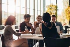 Giovani studenti che studiano intorno ad una tavola in biblioteca Immagine Stock
