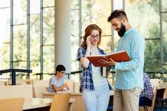 Giovani studenti che studiano nella biblioteca Fotografia Stock