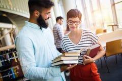 Giovani studenti che studiano nella biblioteca Immagine Stock
