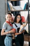 Giovani studenti con il libro e la tazza che studiano insieme e che sorridono Immagine Stock Libera da Diritti