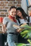 Giovani studenti con il libro e la tazza che studiano insieme e che sorridono Immagini Stock