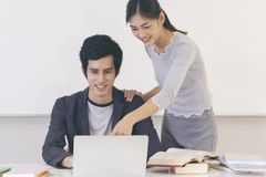 Giovani studenti di college che fanno insieme compito nella classe immagine stock