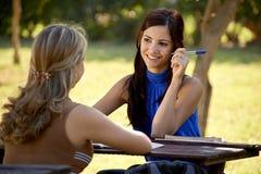 Giovani studenti di college che parlano e che studiano per l'esame dell'università Immagine Stock