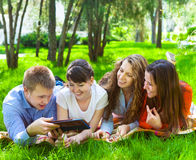 Giovani studenti di college che per mezzo del computer della compressa Immagini Stock Libere da Diritti