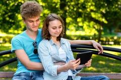 Giovani studenti di estate in un parco all'aperto Si siedono su un banco in città Il tipo sta abbracciando la ragazza Ragazza in  Fotografia Stock Libera da Diritti