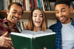 Giovani studenti felici che si siedono in libro di lettura delle biblioteche fotografia stock libera da diritti