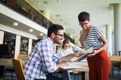 Giovani studenti felici che si siedono nella biblioteca Fotografia Stock