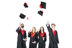 Giovani studenti felici con i diplomi che gettano i cappucci di graduazione isolati Fotografia Stock
