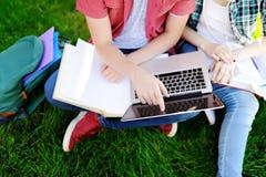 Giovani studenti felici con il computer portatile, i libri e le note all'aperto Fotografia Stock