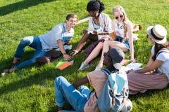 Giovani studenti multietnici che parlano e libri di lettura mentre riposando sull'erba in parco Fotografia Stock