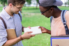 Giovani studenti multietnici che tengono i libri in parco Fotografia Stock Libera da Diritti