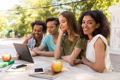 Giovani studenti multietnici felici degli amici all'aperto facendo uso della compressa Fotografia Stock