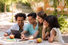 Giovani studenti multietnici sorridenti degli amici all'aperto facendo uso della compressa Immagine Stock Libera da Diritti