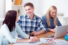 Giovani studenti piacevoli che si siedono alla tavola Immagine Stock