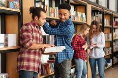 Giovani studenti seri degli uomini che stanno in libri di lettura delle biblioteche Immagine Stock