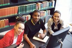 Giovani studenti sicuri alla biblioteca facendo uso del computer Immagini Stock Libere da Diritti
