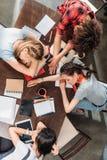 Giovani studenti stanchi che dormono sulla tavola con i taccuini ed i dispositivi digitali Fotografie Stock Libere da Diritti