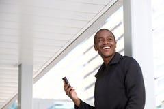 Giovani telefono cellulare e risata africani della tenuta dell'uomo Immagine Stock