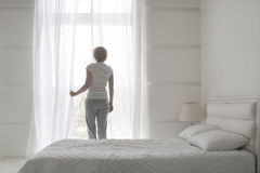 Giovani tende di apertura graziose della ragazza di mattina per rinfrescarsi aria, vista posteriore fotografie stock libere da diritti