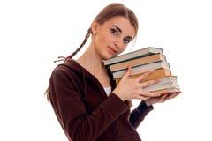 Giovani tenute ragazza-teenager molti libri isolati su fondo bianco Immagine Stock