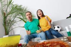 Giovani tifosi delle coppie che guardano incoraggiare gridante della partita immagine stock libera da diritti