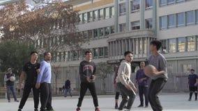 Giovani tipi asiatici che giocano pallacanestro in un'area della via archivi video