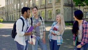 Giovani tipi che ridono francamente sulla città universitaria dell'istituto universitario, amicizia multietnica stock footage