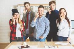 Giovani tipi e ragazze sui loro telefoni Immagini Stock