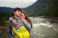 Giovani tipo e ragazza nelle montagne di Altai sul fiume di Katun Fotografia Stock