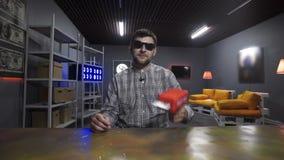 Giovani tiri barbuti del vlogger dell'uomo con le banconote del dollaro dalla pistola di plastica rossa archivi video