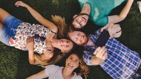 Giovani trascurati che hanno una risata all'aperto che si trova in erba Fotografia Stock