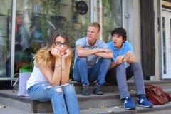 Giovani tre amici che si siedono pavimento nella via, parlando, usando Fotografia Stock Libera da Diritti