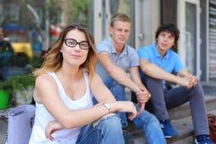 Giovani tre amici che si siedono pavimento nella via, parlando, usando Fotografia Stock