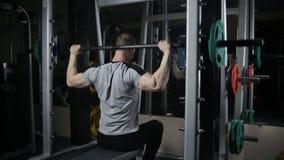 Giovani treni muscolari dell'uomo in palestra stock footage