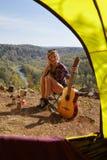 Giovani turisti biondi della donna con la chitarra nel campo sulla scogliera sopra il ri Fotografia Stock