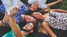 Giovani turisti che riposano sull'erba mentre viaggiando Fotografia Stock Libera da Diritti