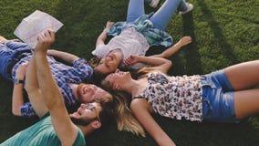 Giovani turisti che riposano sull'erba mentre viaggiando Fotografia Stock