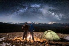Giovani turisti delle coppie di retrovisione che hanno un resto nel campeggio vicino sotto a cielo notturno in pieno delle stelle immagine stock libera da diritti