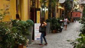 Giovani turisti femminili che passano per la passeggiata con il cane attraverso la città, comperanti al boutique video d archivio