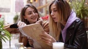 Giovani turisti femminili - dai capelli lunghi in abbigliamento casual che legge mappa della città in caffè all'aperto Progettazi video d archivio