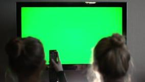 Giovani TV schermo di due e telecomando verdi di sorveglianza biondi dai capelli lunghi di uso archivi video